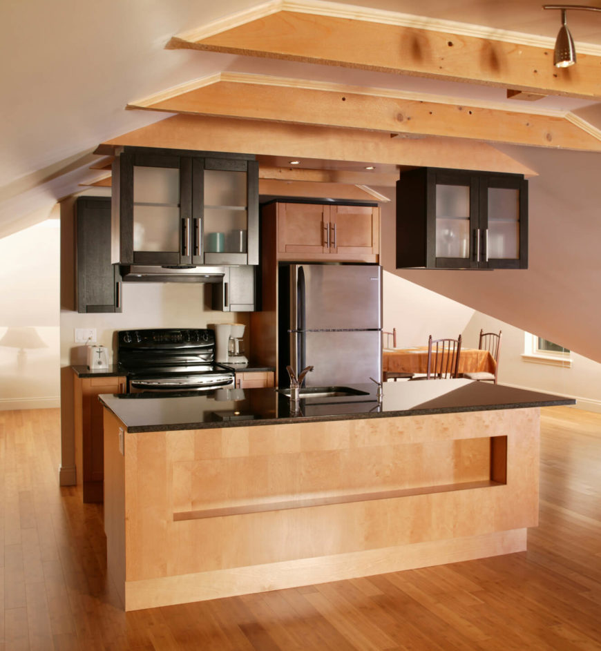 A small kitchen situated against a half-wall in the center of the open-concept living area of an attic living space. The slanted roof makes it difficult to place the kitchen anywhere but in the center of the room. The kitchen itself has glossy black formica countertops and frosted-glass faced wall cabinets.