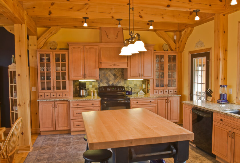 A light wood kitchen with a green tile backsplash and exposed pine beams on the ceiling and walls. The black kitchen island is distressed and has a towel rack on the side. Glass-faced cabinets on either side of the main cooking area display glassware and china. The open kitchen transitions into the dining room along with the tile flooring.