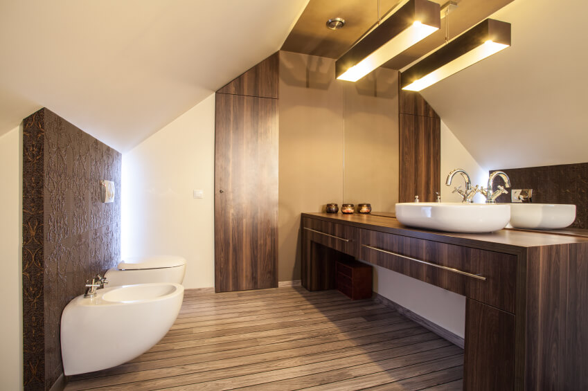 A minimalistic European-style bathroom in wood. A textured accent wall adds visual interest to the smooth, but varied wood grain of the floor and vanity.