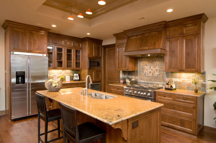 A Small Kitchen With A Beautiful Multi Colored Backsplash And Natural Wood Cabinetry The
