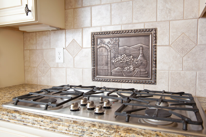 ceramic tile backsplash with a metal medallion above the range in a