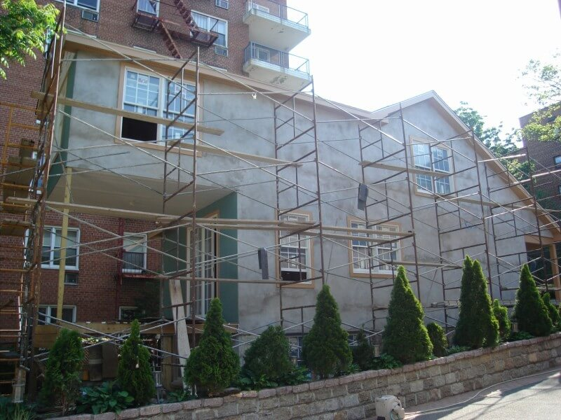 The left side of the home after the new siding has been installed and painting has begun. The owner chose a bright robin's egg blue for the home. At this stage of the renovation, we can also see the additional room above the deck, that adds square footage that the original home didn't have. The chain-link fencing has also been torn down, allowing the stone border wall with topiaries to shine through.