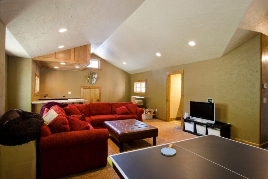 "The bonus room on the second floor has been turned into a family room/game room, complete with an entertainment center and a half-bath off the right wall. The small crawl space door on the far wall leads to additional ""attic"" storage space."