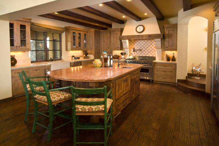 A natural wood country kitchen with two rounded steps that lead from the entryway. The three bright green distressed stools at the island add a bright pop of color. The patterns on the backsplash and on the cushions are common to country style.