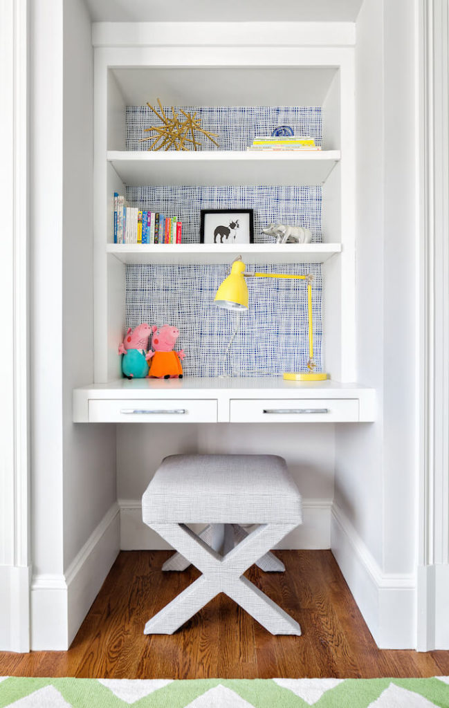"The desk in this children's room has a small upholstered stool that can be swapped out for a larger seat as the child grows. The back of the built-in desk is a blue and white ""cheesecloth"" pattern that breaks up the neutrals."
