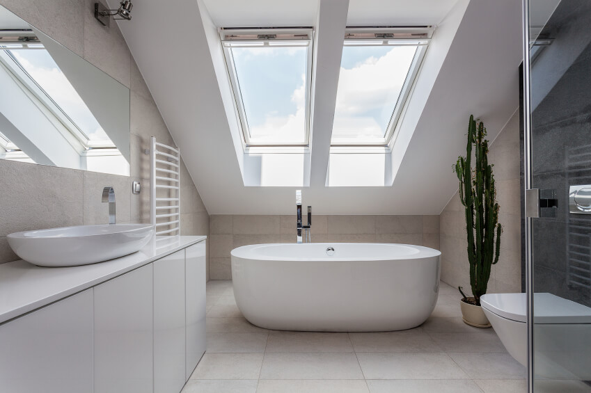 A White Bathroom With Sleek Modern Fixtures And Two Skylights Above The  Deep Soaking Tub.