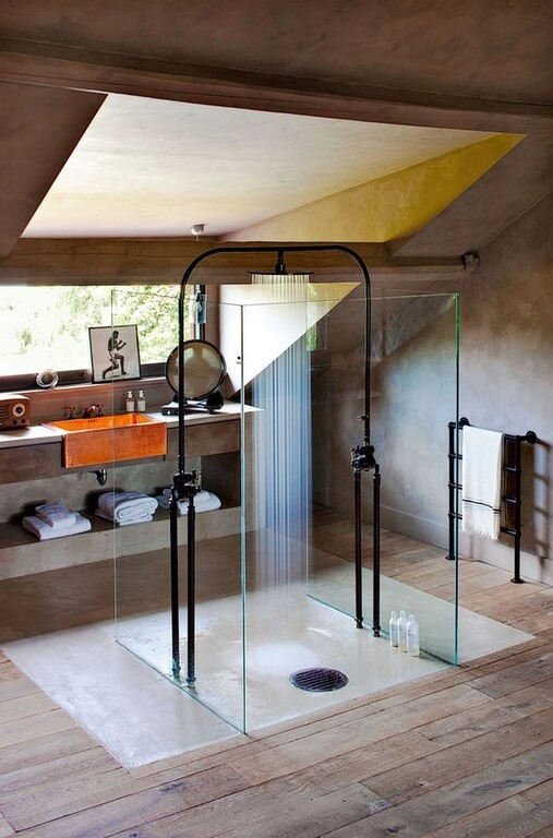 An industrial style bathroom with a centered glass-enclosed shower with a centered shower head. A towel rack is formed with pipes.