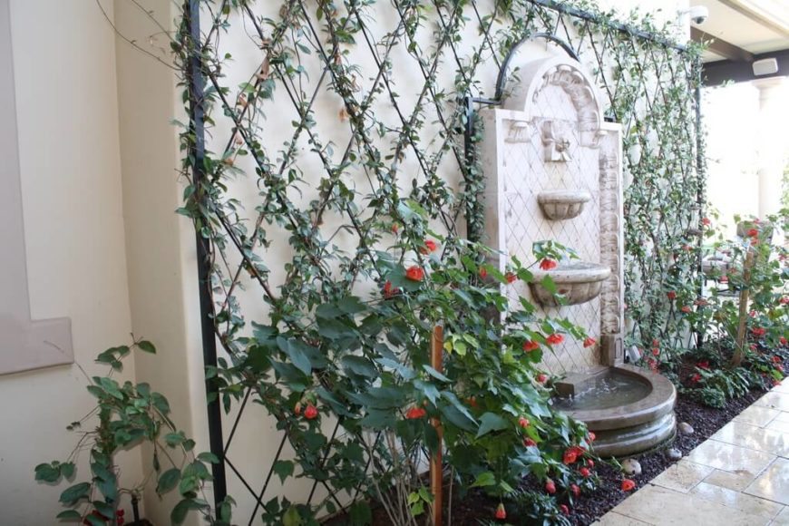 a diamond patterned lattice surrounds a wall fountain - Trellis Design Ideas