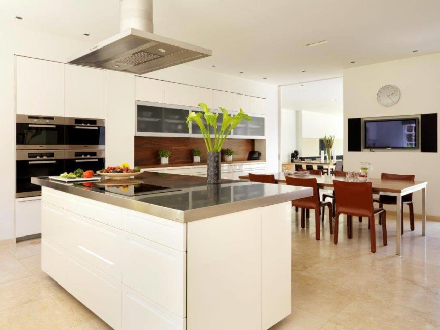 A view from behind the kitchen island's stainless steel countertops to the breakfast table and shelving unit to the rear of the room. On the wall between the kitchen and the formal dining room is a television.