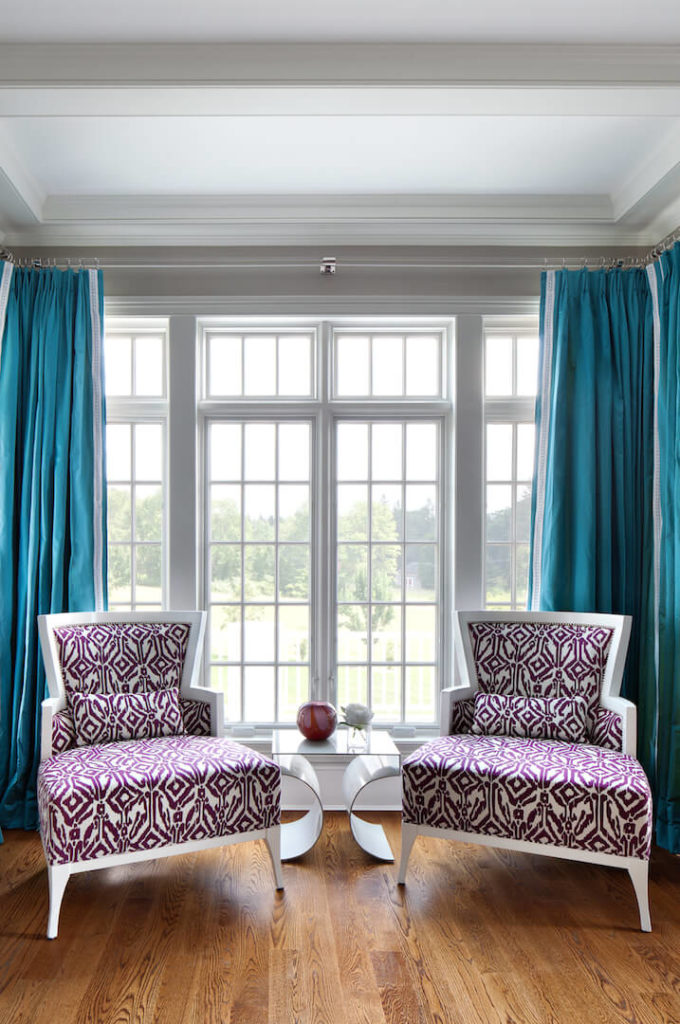 A closer look at the sitting room in white and purple in front of the large windows. Between the two chairs is a modern side table with a few small decorative pieces. The bold turquoise drapes behind the chairs is a bold statement in color.