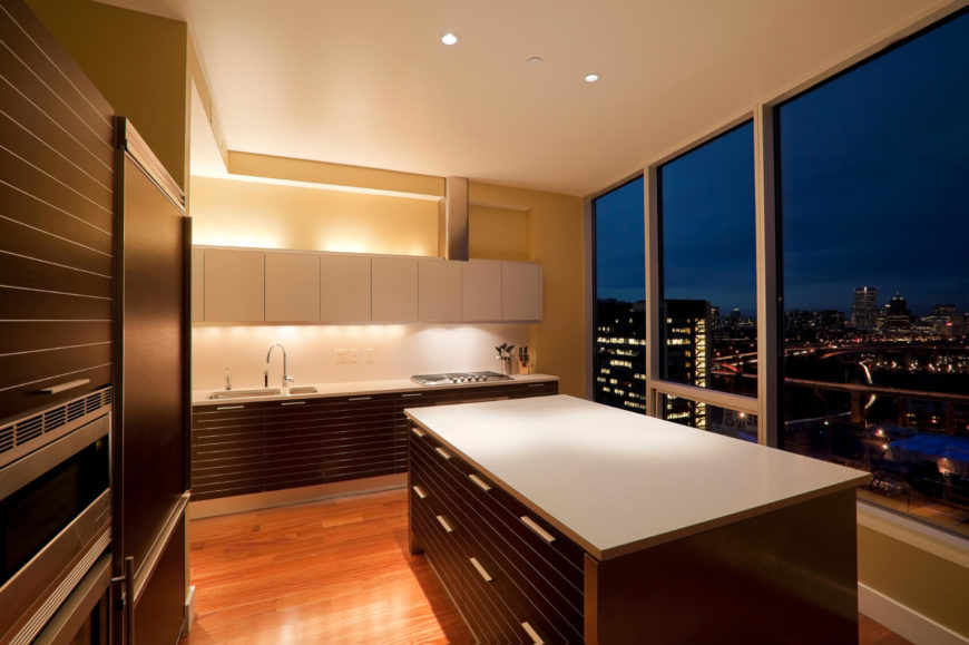 A minimalist kitchen with lined dark wood cabinetry and white matte countertops overlooking a balcony patio and the city at night.