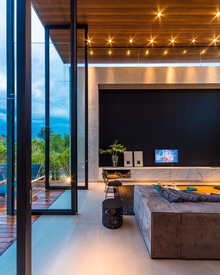 On the side connecting with the patio, we see the giant glass pivot doors, fully opened here to blend the interior with the outdoors.