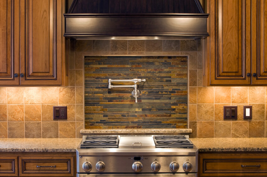 A Beautiful Kitchen In Shades Of Brown With A Stone Backsplash And An Inset  Center Focal