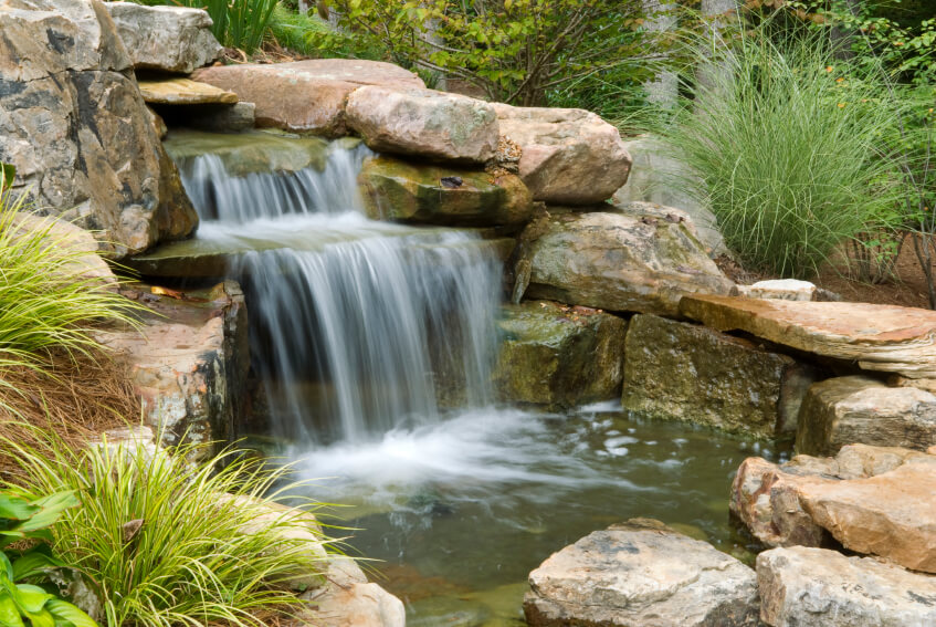 This Water Feature Focuses On The Large Waterfall Tumbling Into A Small,  Shallow Pool At
