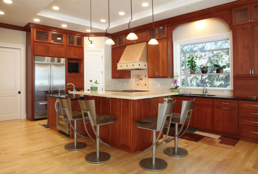 A Contemporary Kitchen With Rich Red Toned Cabinetry And Sleek Metallic  Backed Barstools Around The