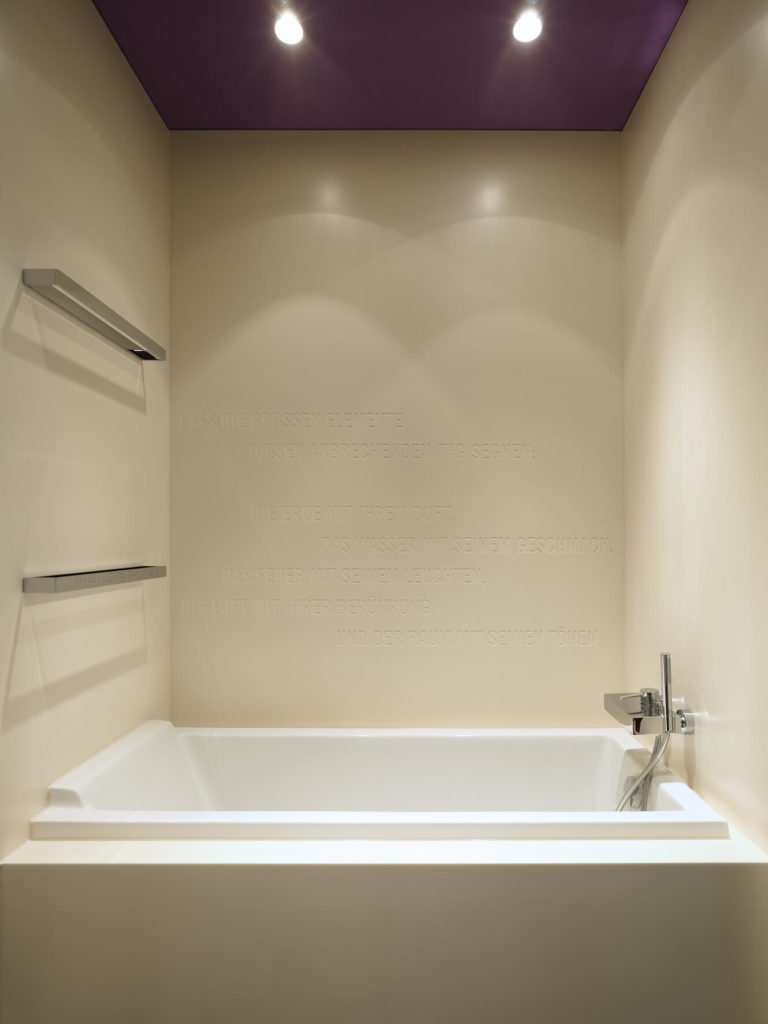 The bath is designed with text etched into the wall, below a bold purple ceiling.