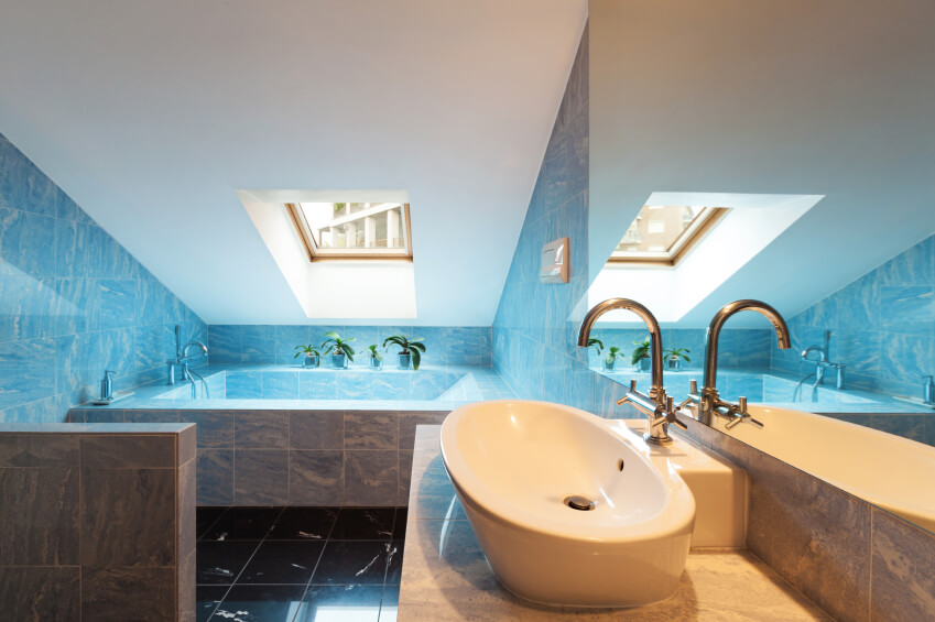 A gray bathroom that seems to glow blue in the natural sunlight coming from the skylight.