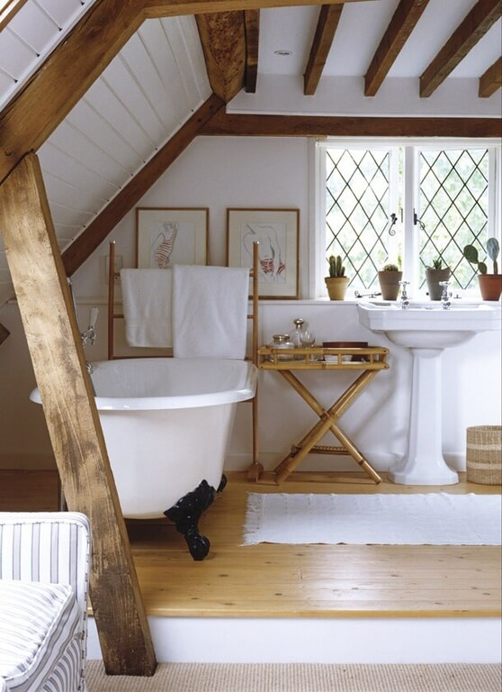 A stylish attic bathroom with a claw foot bathtub and a mix of natural materials including bamboo and barn wood. The pedestal sink is near a latticed window with succulents basking in the natural light.