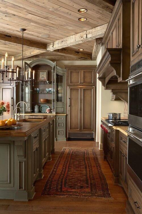 An L Shaped Rustic Country Kitchen With A Red Floral Patterned Rug Between The