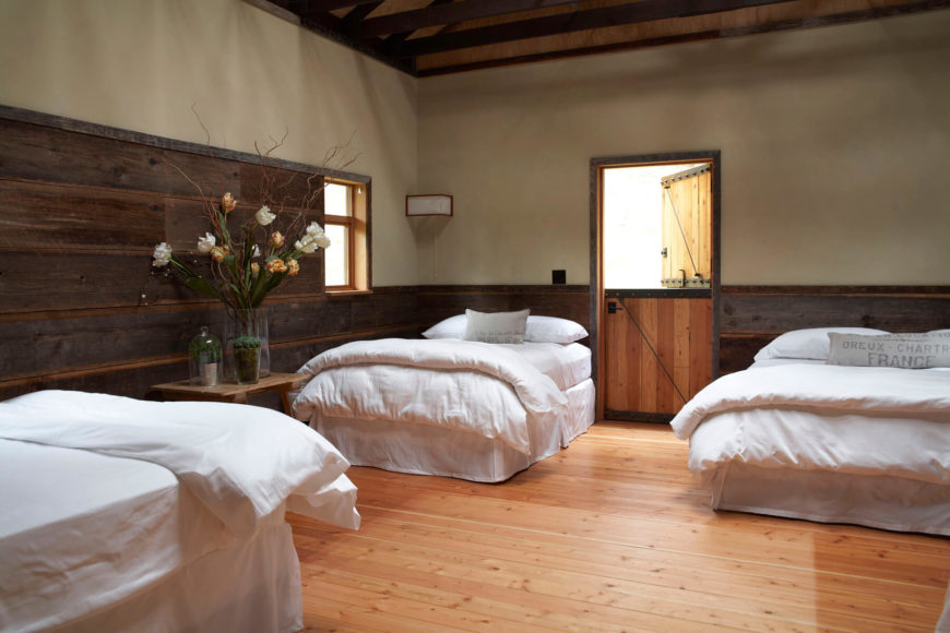The bunk room has matching double beds in white bedding. The walls are a combination of natural wood paneling and cream painted walls. The original barn door leads directly outside.