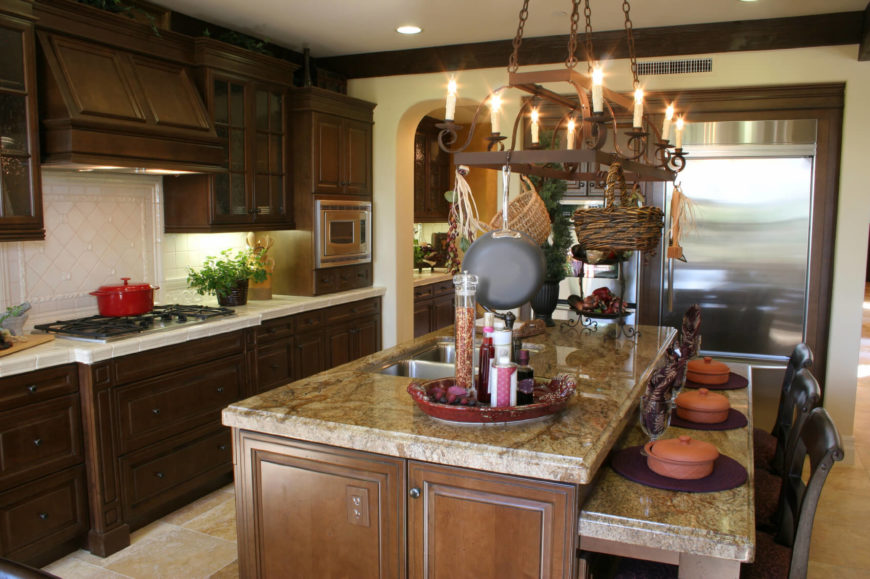 A Country Kitchen With A Two Tiered Kitchen Island With Seating For Three.  The