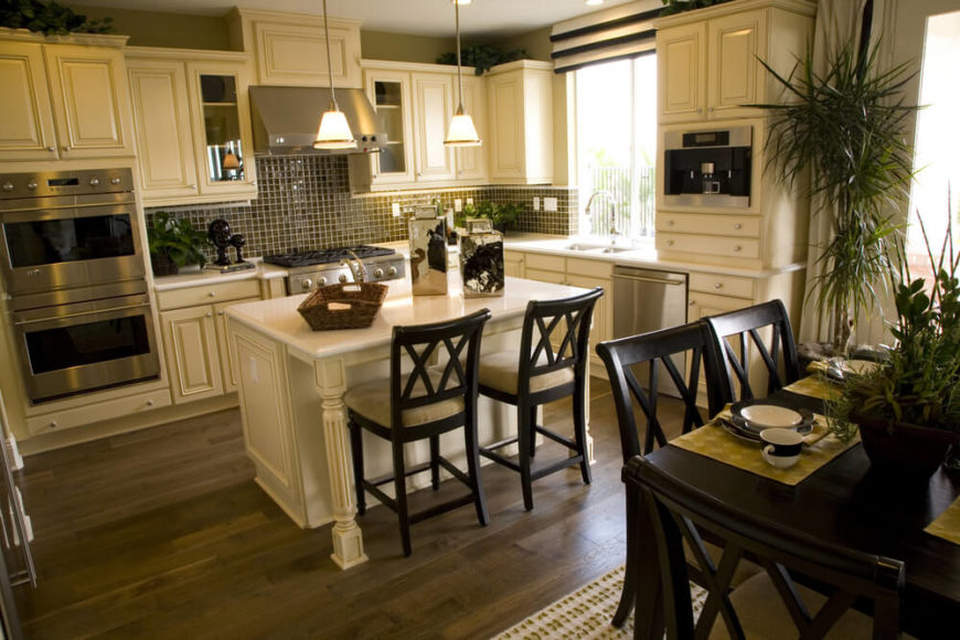 A White Kitchen With Glass Tile Backsplash And Hardwood Flooring. A Small  Kitchen Island Part 39