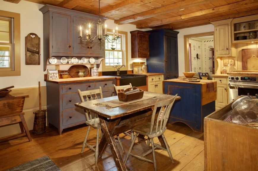 A Rustic Country Kitchen With Distressed Table Chairs And Cabinetry In A Variety Of