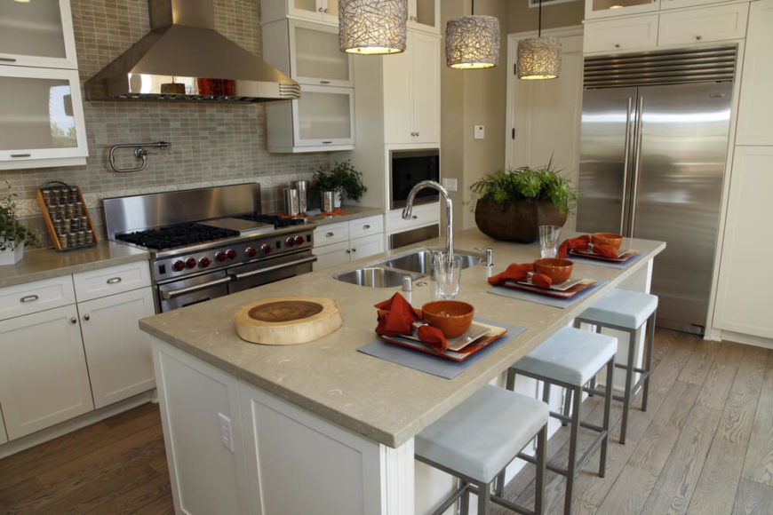 A Contemporary Kitchen In Gray And Beige With Bold Accents Of Orange. The  Wide Stove