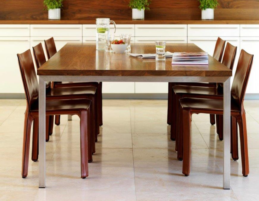 The hardwood breakfast table has lighter legs than the top, and the slim dining chairs are in a much darker tone. On the wall behind the table is a long wooden countertop with cabinetry above and below it. The countertop is home to several potted herbs.