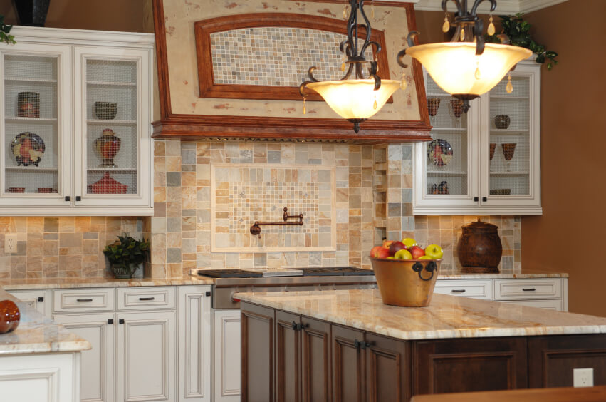 A multi-colored stone backsplash with tiles in varying shapes. A section in  the