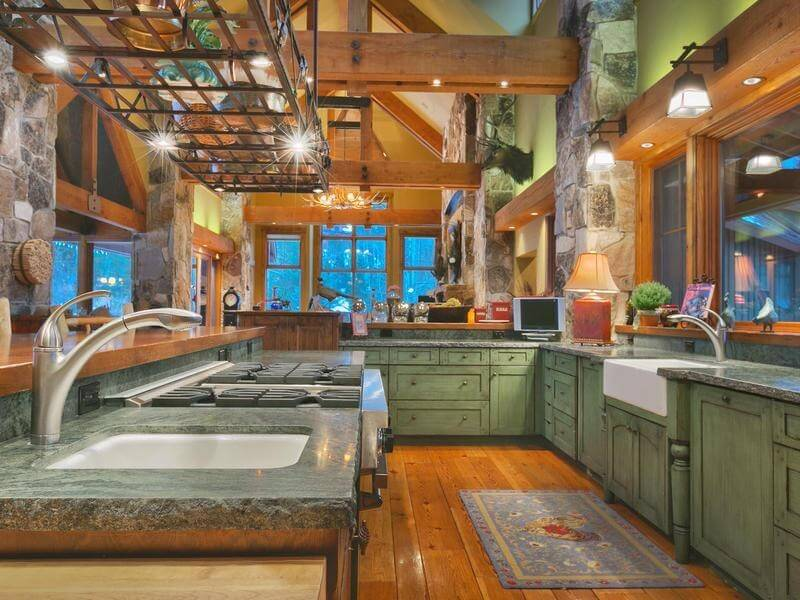 A Rustic Country Kitchen In A Dusty Green And Granite Countertops With A Rough Hewn