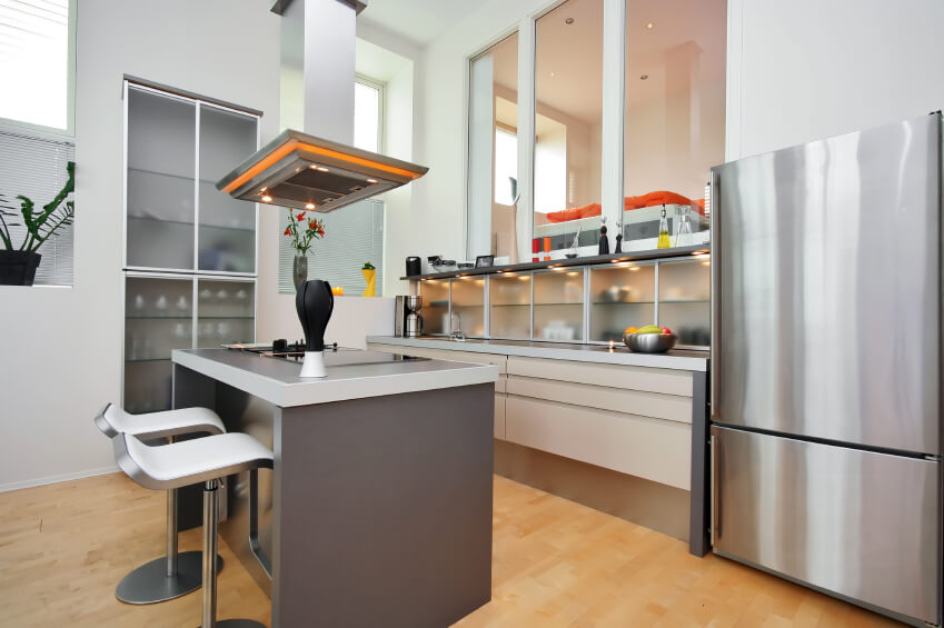 A modern kitchen with frosted-glass cabinetry and shelving on the side of  the room