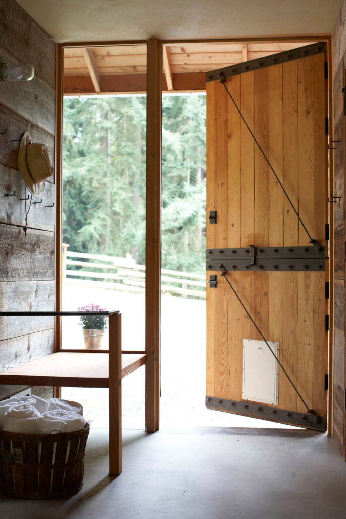 Another of the barn's bathrooms, with a door and a bench with a basket of towels next to it. Added to the barn door is a pet door.