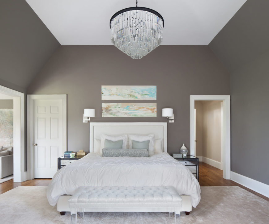 The master suite has a delicate, light color palette with a gray-green rich wall color and mint accents. Bolder, yet still elegant colors are brought into the room via the two paintings above the head board. Through the archway on the left is the adjoining sitting room.