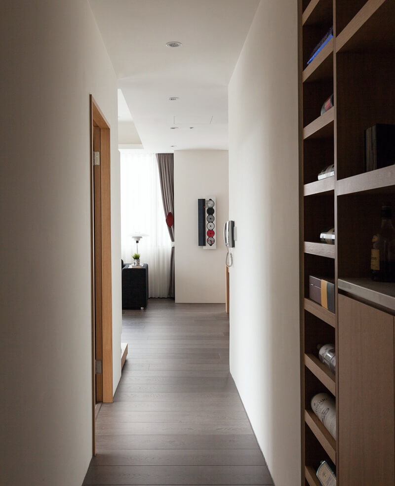 The hallway off of the living room has more built-in shelving and doorways to the bathroom, bedroom, and home office.
