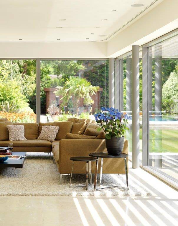 The sunroom is furnished like a traditional indoor living room, with large, seamless floor-to-ceiling windows that allow the occupants to enjoy the warm sunlight and garden scenery.