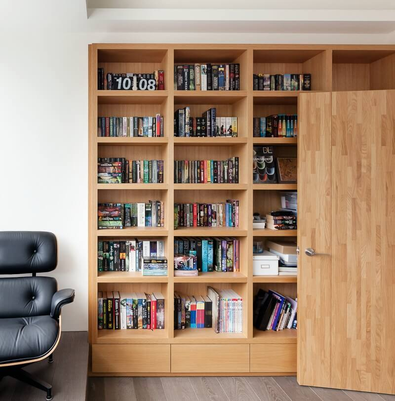 The home office features a higher tier of flooring where the desk and chair are located, and beautiful natural wood bookcases on the lower section.