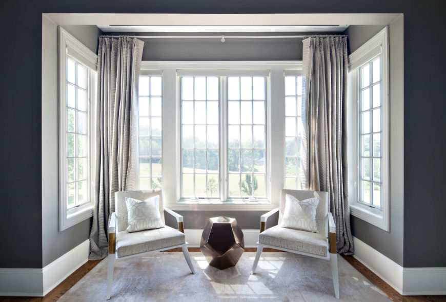 A small sitting area by the bay windows of the master suite. The contemporary chairs are matched with a small area rug and a metallic side table in bronze. The subtle striped curtains behind the seating area add a dimension of pattern.