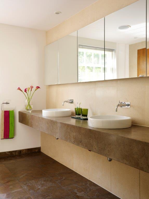 One of the home's three bathrooms, with a floating sink in brown granite and a beige tile backsplash. The his-and-hers vessel sinks have wall mounted faucets in chrome.