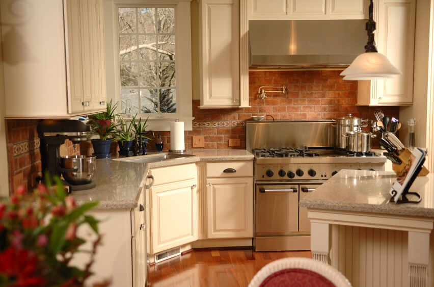 A Contemporary Country Kitchen With A Dusky Red Brick Backsplash And Light Ivory Cabinets With Delicately