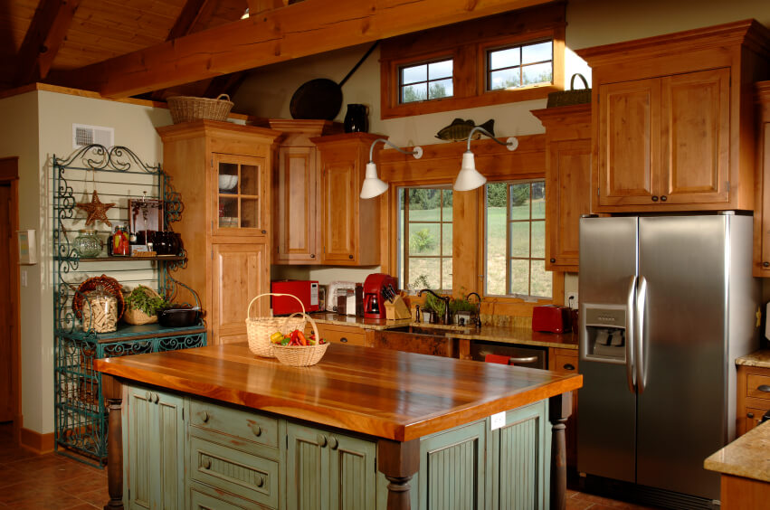 A country kitchen with a pale green and polished wood island and an iron baker's rack that's been painted a bright green.