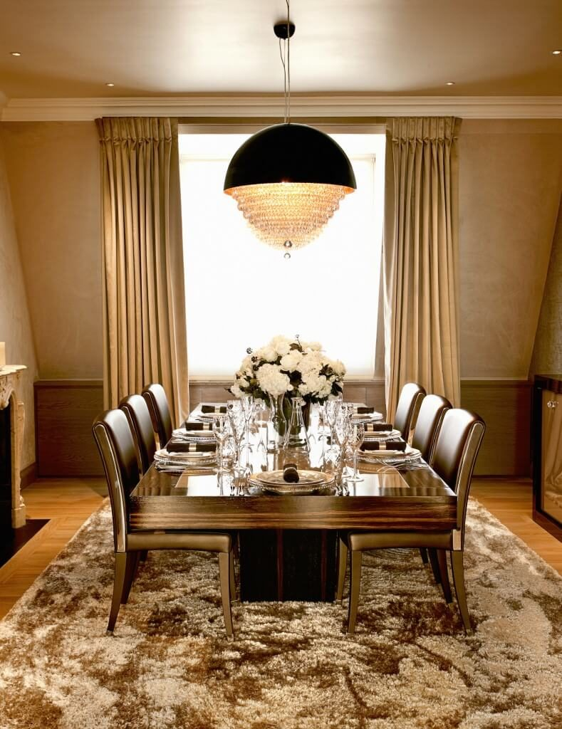 the thick luxurious area rug beneath the dining table runs almost to the edge of