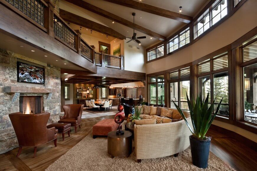 Great Room Designs With Fireplace Part - 32: A Spacious Curved Living Room With Soaring Ceilings, Overlooked By The  Upstairs Hallway. The