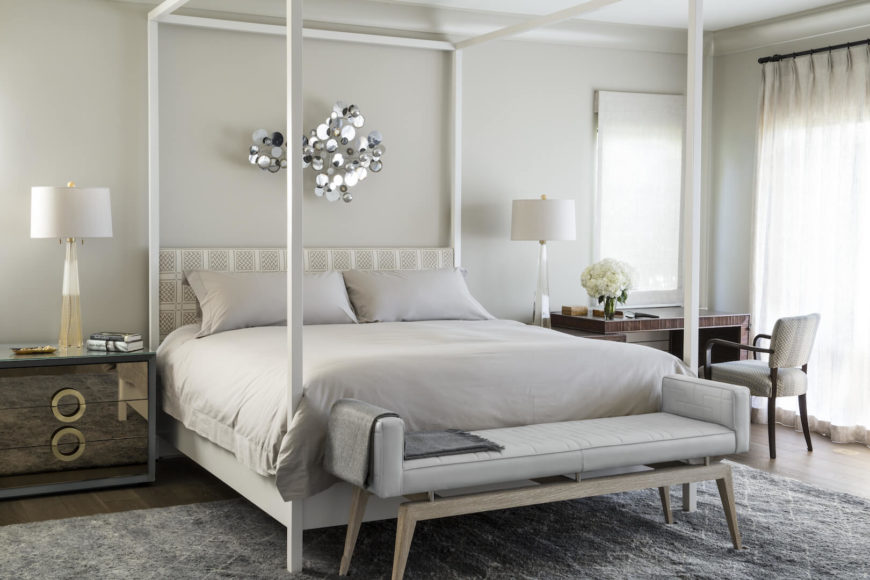 The primary bedroom is an understated white with accents of deep brown. The modern sculpture above the bed is an eye-catching statement piece.