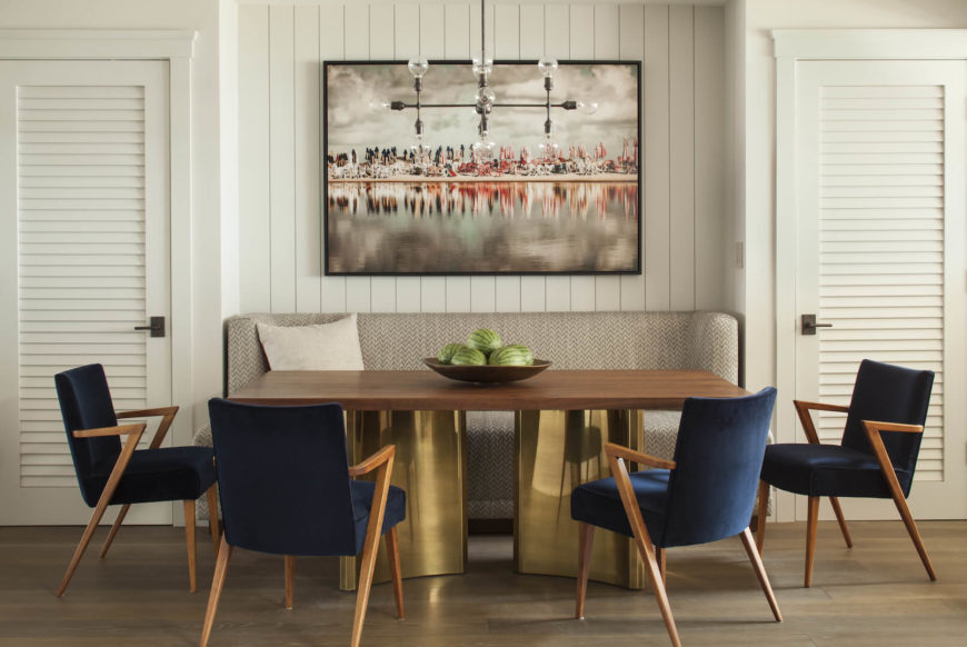 The more casual breakfast room has a gorgeous statement dining table with a custom hardwood top and a pair of brass bases from the 70s.