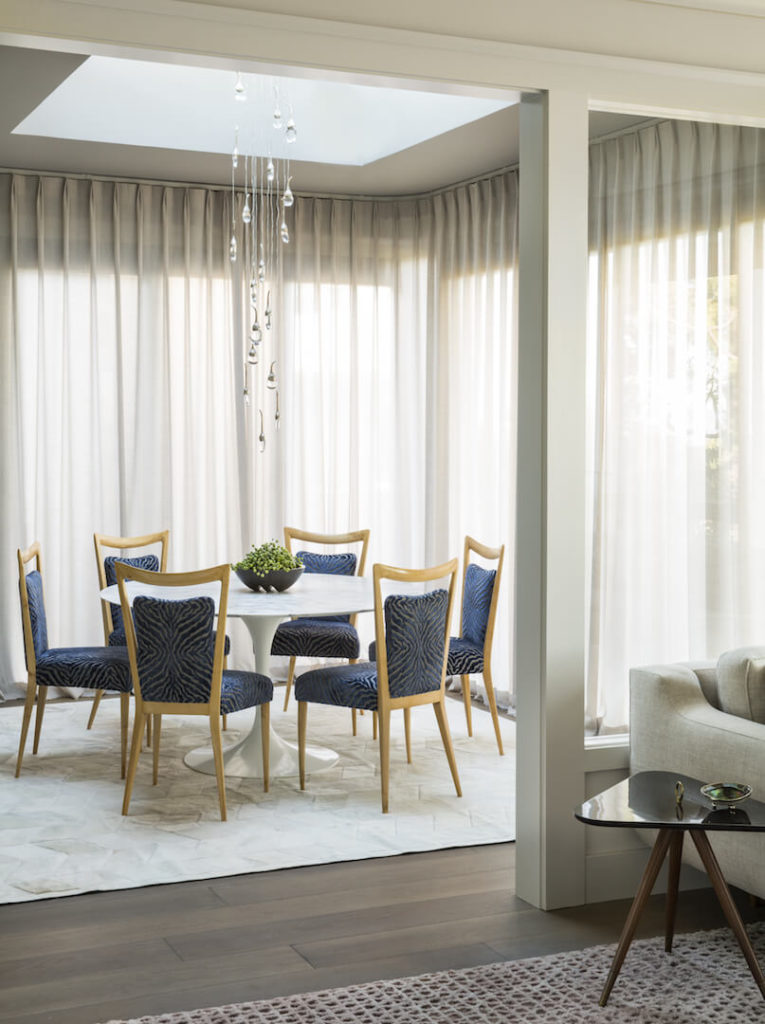 The formal dining room comes off the spacious living room an combines smooth lines and pristine white with a blue zebra pattern and soft yellow wood chairs.