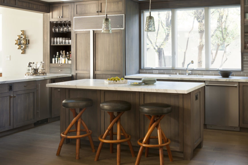 Kitchen with center island and stools, light wood cabinets.