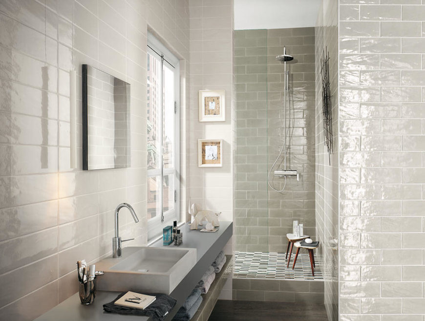 This light and bright bathroom is in white and dove-gray tiles. For contrast, the floor of the shower stall is in striped tile. Towel storage is beneath the slim vanity.