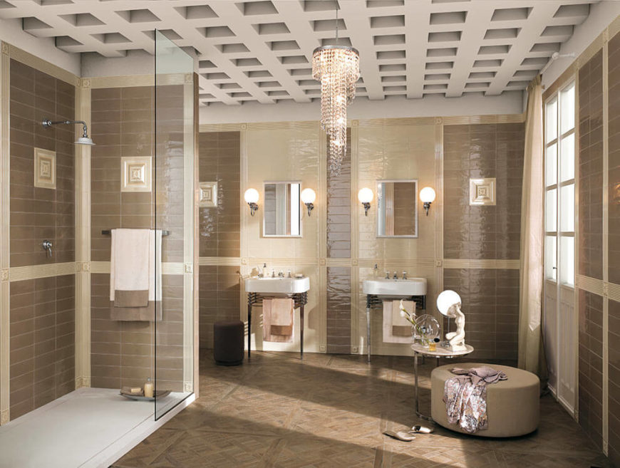 Another luxurious bathroom with a parquet floor and floor-to-ceiling tiling. The lighter cream tiles are separated from the darker brown tiles by ceramic molding. The elegance of the room is ramped up further by the chandelier hanging from the deep coffered ceiling.