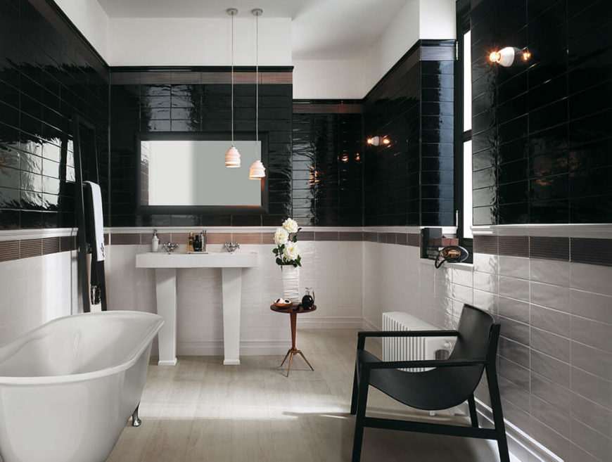 This modestly sized bathroom is tiled in white, brown, and black. The lower half of the room is in white, with a strip of brown tile separating the black tile from the white. The result is a gorgeous, sophisticated bathroom that is resistant to mildew and mold.